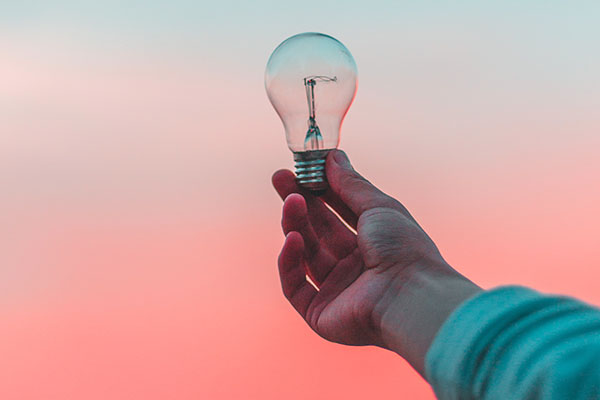 photo of a lightbulb being held against a vibrant sky