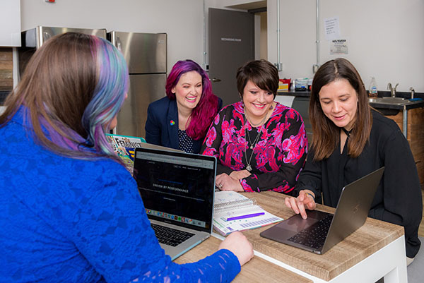 Four females at a table with laptops in discussion